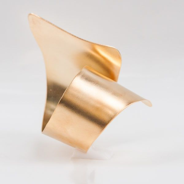 Cast from polished gold-plated brass, this wide cuff bangle is designed by a minimal scuplure form, that that comfortably slips over your hand. Wear yours solo or stacked with similar styles.