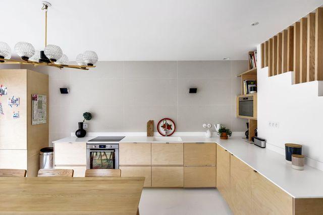 A gauche, le réfrigérateur est caché dans la colonne. Malin, le micro-ondes et les livres de cuisine s'invitent dans une niche graphique, à droite sous l'escalier !