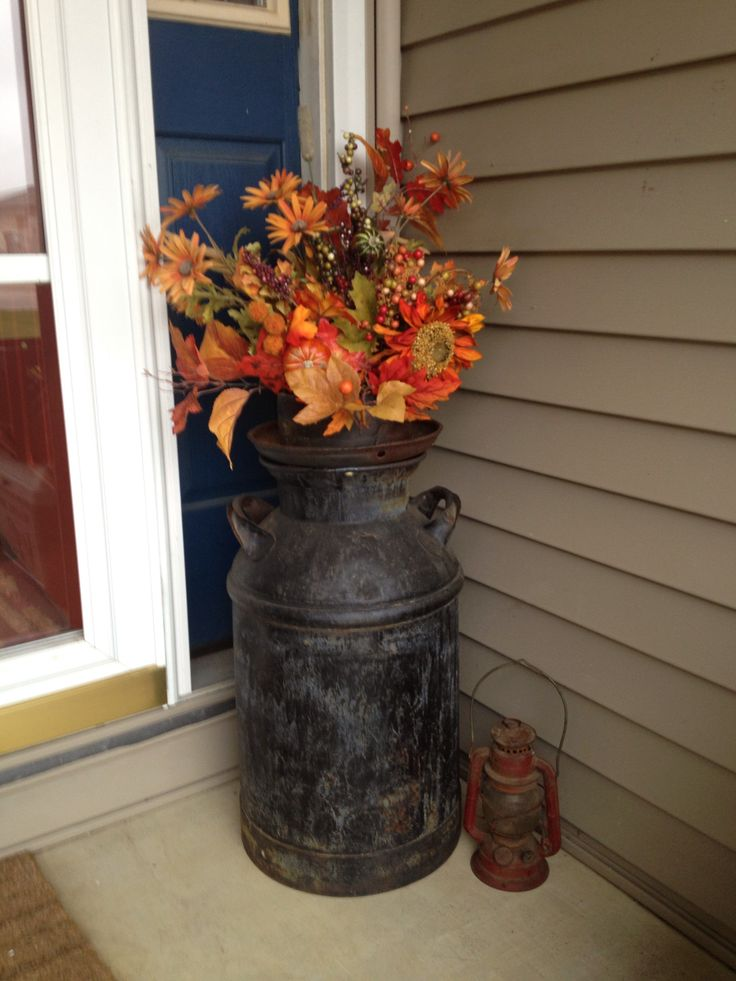 Old milk can with fall floral arrangements for the front porch.