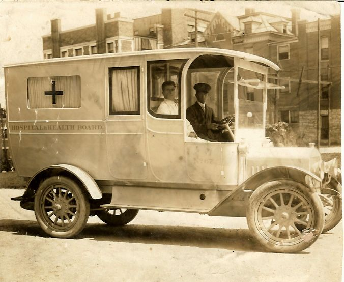 "Image of an early ambulance. The lettering on the side of the ambulance reads ""Hospital and Health Board"". The hubcaps are clearly marked GMC. The tires are marked Goodrich."