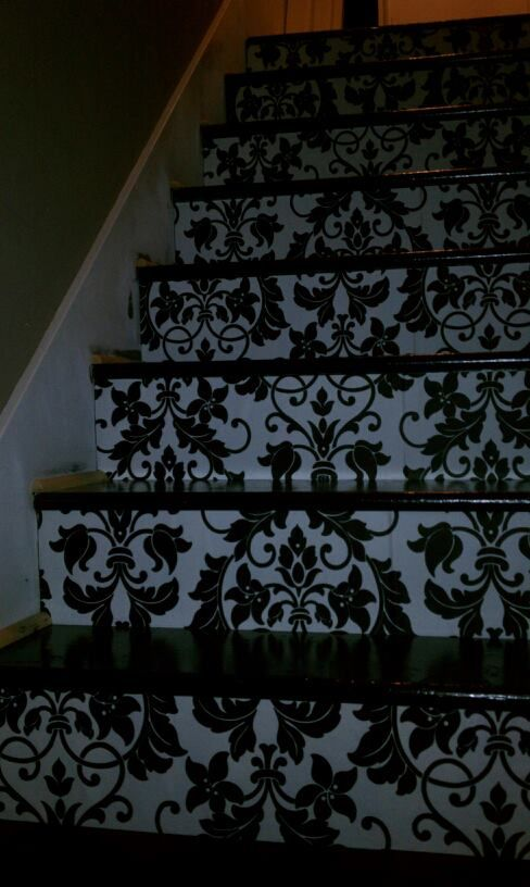 wallpapered the rise of the stairs! still have to finish painting the trim...
