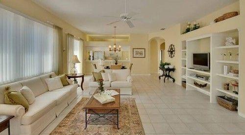 Dieses offene Konzept Wohnzimmer ist in den Farben Creme von den weißen Wänden mit einer fast undeutlich weißen Deckenventilator, cremefarbene Wände, weißen offenen Regalen und getönten Lichtwand Bodenbelag