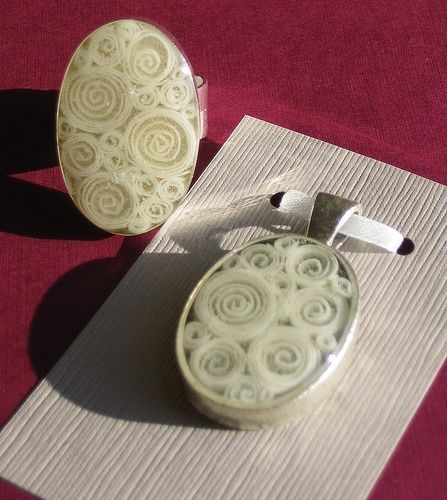 Curled pieces of card stock cast in resin inside of a sterling silver plated ring and pendant bank.