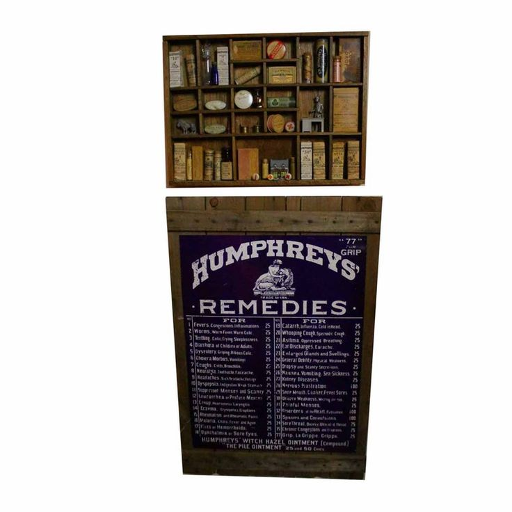 "A collection of Antique Humphreys' Remedies homeopathic items with a menu of products, display box, and more. This collection of items for display includes a wood advertising sign with a blue panel that lists seventy-seven categories of illness with prices and number codes for remedies; maladies include ""Cholera Morbus,"" ""General Debility,"" ""Catarrh, Influenza, Cold in Head,"" and ""Dyspepsia."" A divided wooden display box contains Humphreys brand homeopathic products as well as over the…"