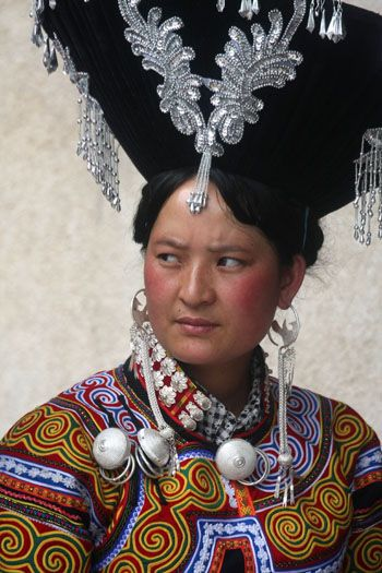 China   Yi woman with a traditional decorated hat   Puge, southern Sichuan province.  © Boris Kester