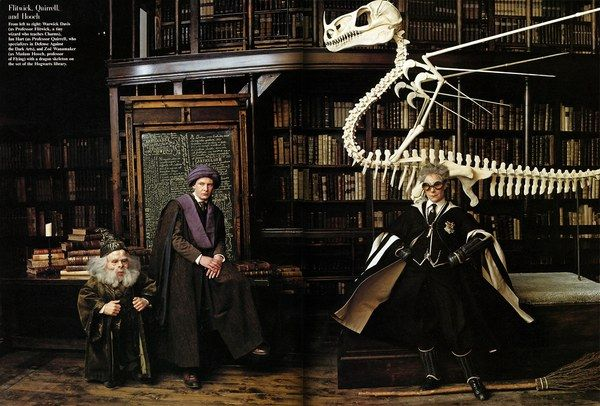 __Flitwick, Quirrell, and Hooch__      From left to right: Warwick Davis (as Professor Flitwick, a tiny wizard who teaches Charms), Ian Hart (as Professor Quirrell, who specializes in Defense Against the Dark Arts), and Zoë Wanamaker (as Madame Hooch, professor of Flying) with a dragon skeleton on the set of the Hogwarts library.