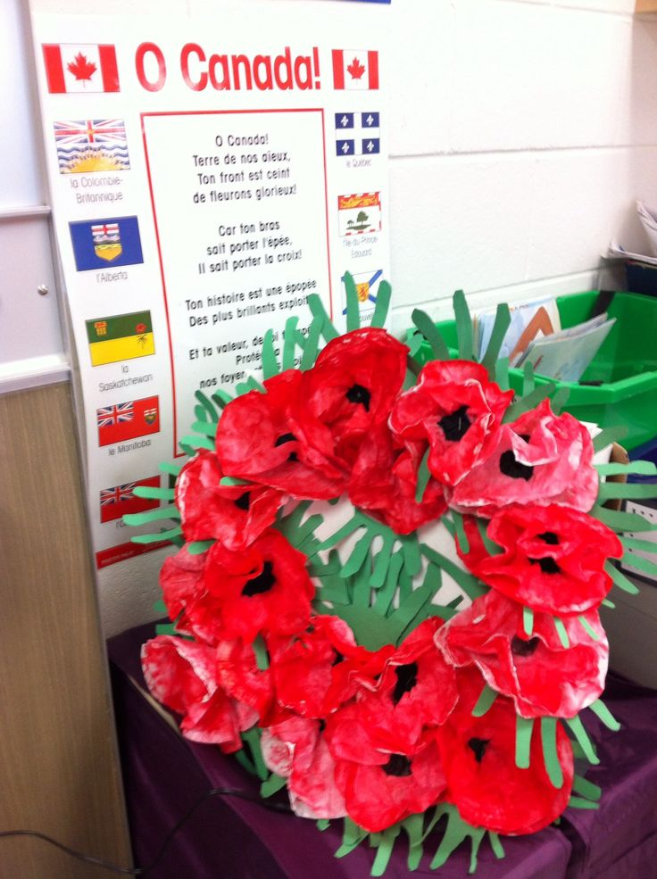Remembrance Day wreath. Couronne de Jour du Souvenir. Made with coffee filters coloured with markers, then sprayed with water so colours bleed. Green hand leaves. All glued to pizza box stand.