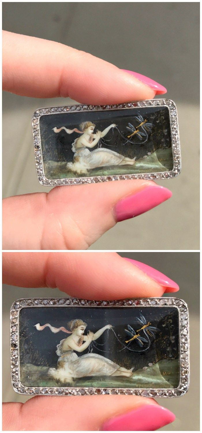This antique brooch contains a painting of a girl in classical dress flying two dragonflies on delicate leashes made of ribbon. Spotted at Joden.