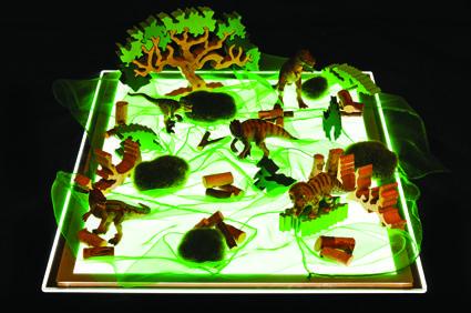 Create a dinosaur mini world on a light box.
