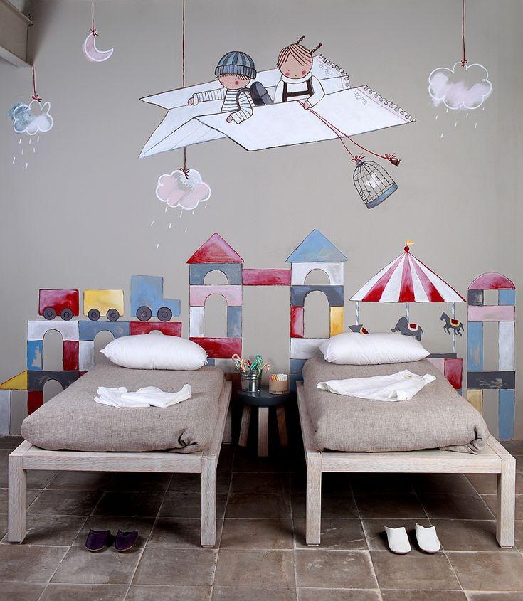 Mural para habitacion infantil, 2 niños en un avión de papel, sobrevolando una ciudad de juguete