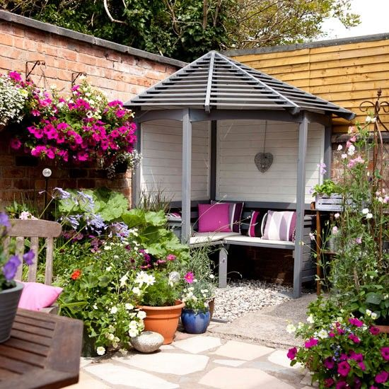 This small, walled courtyard garden has been turned into an ideal summer retreat perfect for socialising and relaxing. The eye is immediately drawn to the charming grey and cream painted arbour come summer house. Pretty hanging baskets and pots bursting with pink petunias pick out the fuchsia scatter cushions within the inviting space