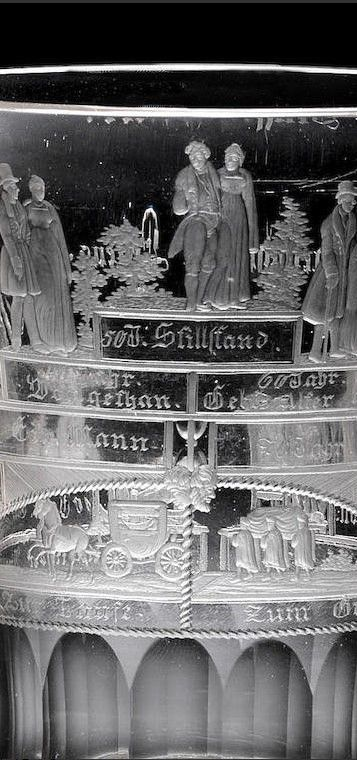 Detail -  A North Bohemian engraved 'Lebensalter' beaker by Anton Simm, Gablonz, circa 1830 The flared campana form decorated with a terraced bridge, the underside of the bridge divided into two by an hourglass, Janus head and a ropetwist border, a coach and horses to the left inscribed Zur Taufe (To the Baptism), and six men carrying a coffin to the right inscribed Zum Grabe (To the Grave), the steps of the bridge surmounted by figures representing 'The Ages of Man', from a child in the…