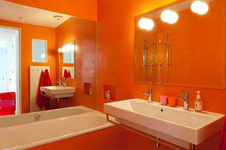 orange bathroom in a house that´s mostly white with orange furniture accents.