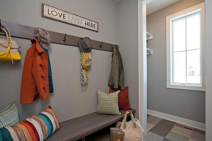 Gray family friendly mudroom features gray walls with white moldings lined with a long wood bench under a row of hooks alongside a multi-colored tiled floor.