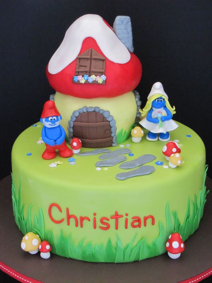 Smurf Birthday Cake - This Smurf birthday cake was for a little 8 year old boy.  Everything is edible.  The characters are made out of gumpaste as well as the small mushrooms.  The mushroom house is cake, but the mushroom top is rice crispies.