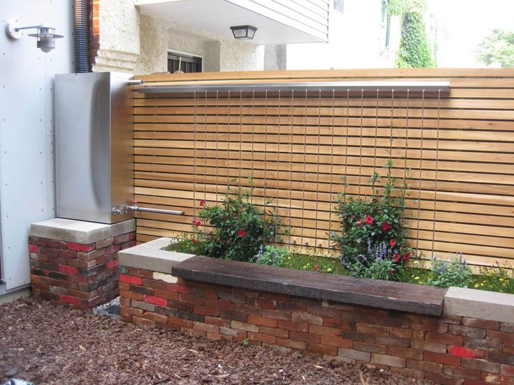 Add more functionality. Water storage and irrigation are combined in this modern take on classic rainwater storage. Rather than hide the workings, the storage unit and custom overflow tank are part of the overall patio design.