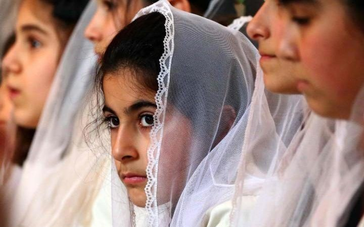 Syrian Christian girls attend a Good Friday mass at the Syriac church of the Holy Virgin in the northeastern city of Qamishli, on April 14, 2017.