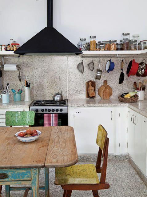 Cocina de una casa remodelada con piso vintage de granito, barral metálico para colgar utensilios, estantes de almacenamiento y campana de hierro.