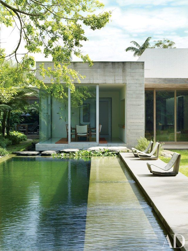 Architect Isay Weinfeld designed this contemporary-style home for an art-loving family in São Paulo. The swimming pool features a chemical-free filtration system, utilizing a separate regeneration area filled with aquatic plants and fish for water purification. | archdigeset.com