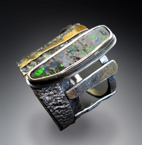 Boulder opal in silver with 22k accents in open work ring featuring contrasting textures in silver