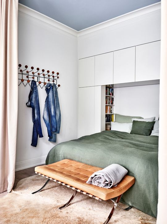 This bedroom from Elle Decoration has a wall of built-ins that envelops the bed.