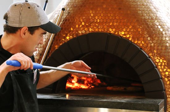 """Brass colored """"penny"""" tile mosaics dress this spectacular pizza oven -- www.hudsontilesupply.com"""