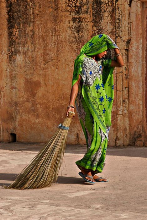 INDIA: A woman with a broom. Sweeping, keeping the yard clean is a matter of pride, yet streets of cities are littered with garbage. Why?