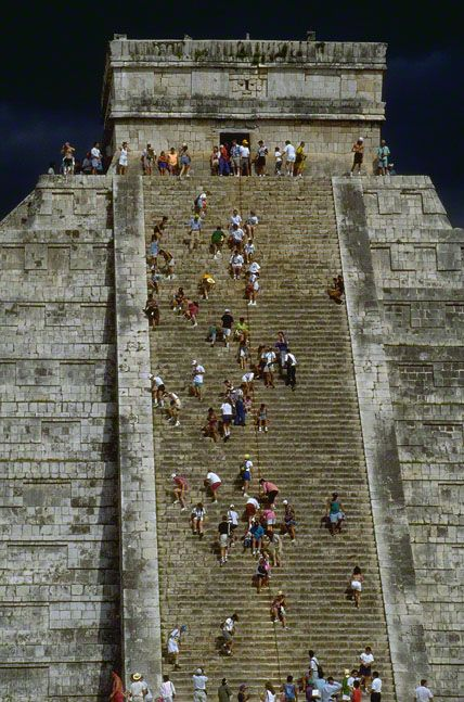 Tourists climb the steep stairway up the Mayan pyramid of Kukulkan at Chichen Itza†. Yucatan, Mexico.