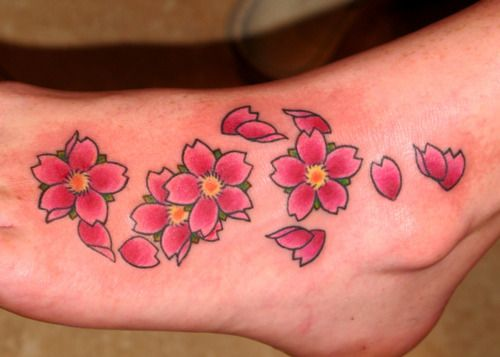 Foot cherry blossoms Little red and yellow cherry blossom flowers floating on the side of a foot with green leaves and single petals. Small pink exotic flower tattoo on foot Cherry blossom flowers have a simple yet sweet design. These flowers aren't attached to a branch. They just look like ...