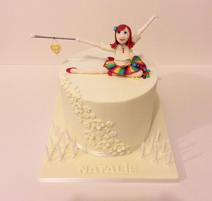 13th birthday cake for the daughter of a friend. This was a collaboration with my caking friend, where we split the work. The ivory decor hides a rainbow cake underneath :-). The cake was covered in buttercream, and we seem to be getting the hang of making this a bit smoother. The figure on top is a little dancer with her majorette baton.