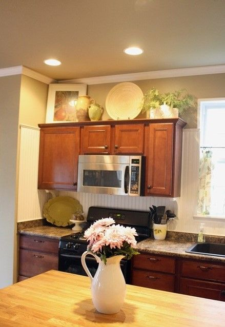 Decorating over your kitchen cabinets. Brackets under cabinets, wainscoting applied high, color combo and a kitchen layout that is very typical of what we have around here.