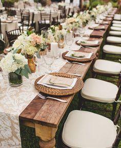 (Foto 14 de 14) Mesa de boda alargada, con camino de mesa de encaje y platos con base de mimbre, Galeria de fotos de La mantelería, la vajilla y la cubertería en tu boda también son importantes