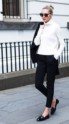 European flair. She is wearing a white turtleneck sweater with narrow black pants and patent black loafers. Carrying a black blazer. Sunnies. Style Planet
