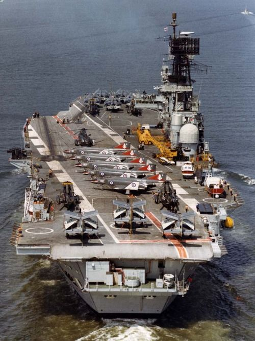 The old Ark Royal (R09) served from 1955 until 1978 and during her final decade carried FG1 Phantom fighters and Buccaneer long range strike aircraft capable of delivering tactical nuclear weapons. She gave potential enemies sound reason for prudence and diplomacy rather than military gambles. Here Gannet AEW aircraft are parked across the stern, five FG1 Phantoms along the flight deck and some Buccaneers on the bow.