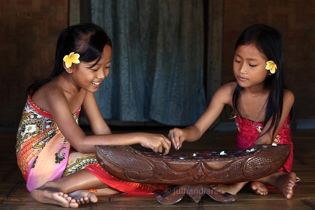 Children playing a tradition Javanese game called Dakon in Indonesia.