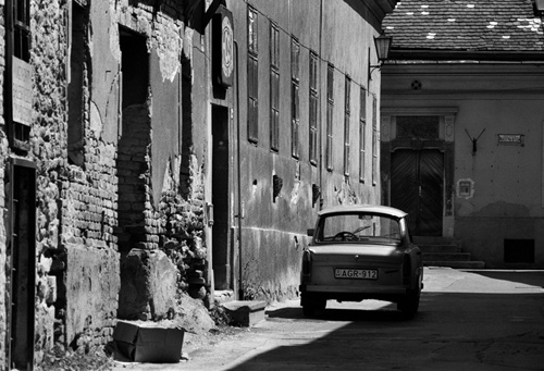 A Trabbant in an alley: a classic scene from the 90s. Pollution regulation now means the few Trabbies are seen on Hungary`s streets. This tiny East German car, made from resin and cardboard, is now a collector`s item.