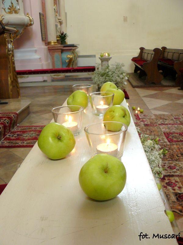 delikatna dekoracja kościoła - gipsówka świeczki i jabłka przed ołtarzem