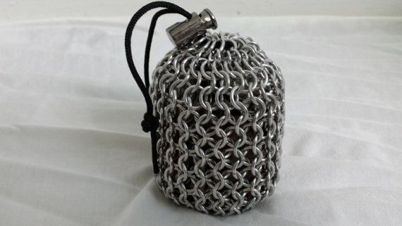 "Chainmail Dice Bag Small. This chainmail dice bag is made out of 16g bright aluminum. It measures roughly 2 1/2"" wide and 3 1/2"" tall. It can hold a lot of items such as change, dice, marbles, and much more. It is 100% handmade from coiling the wire, saw cutting the rings, and then weaving them into a pouch. The bag is fastened by a parachute cord and closed off by a cord lock."