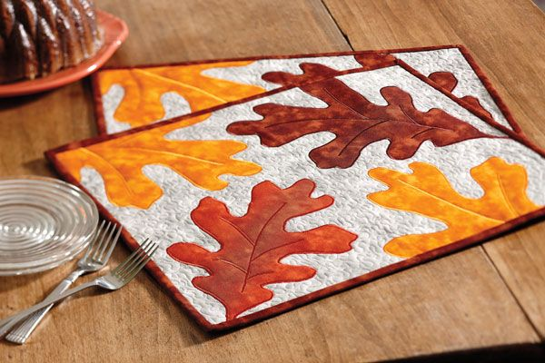 Large oak leaves in an earthy palette fall across an autumn gray sky in these contemporary placemats.