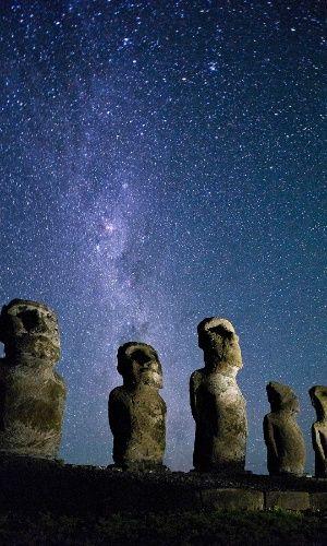 Estátuas Moais, na ilha de Páscoa sob o céu limpo a noite. A pouca luz da ilha polinésia faz do local ideal para observação estelar. O local ao sul do Pacífico, fica a 4.100 km do Taiti e a longos 3.700 km da costa da América do Sul