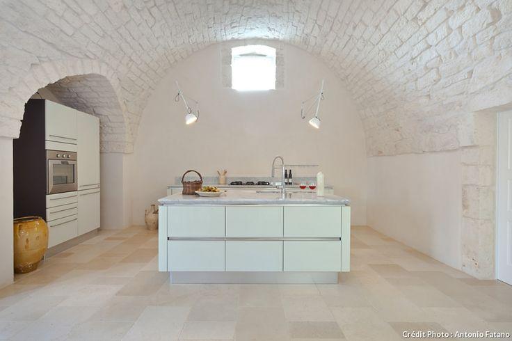 Dans le gîte italien Masseria Grottone, un gîte rural d'exceptio, la cuisine est aménagée dans une pièce avec un plafond en arcs voutés.