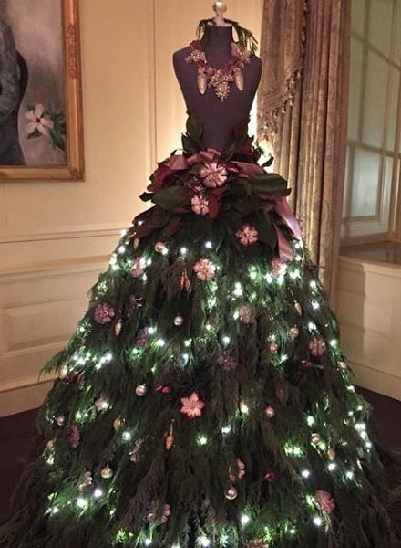 A mannequin is used to create a beautiful Christmas tree. Lush greens were adds to make a skirt with tucked in white lights added between layers of green. Small flowers were added as well. A neckla...