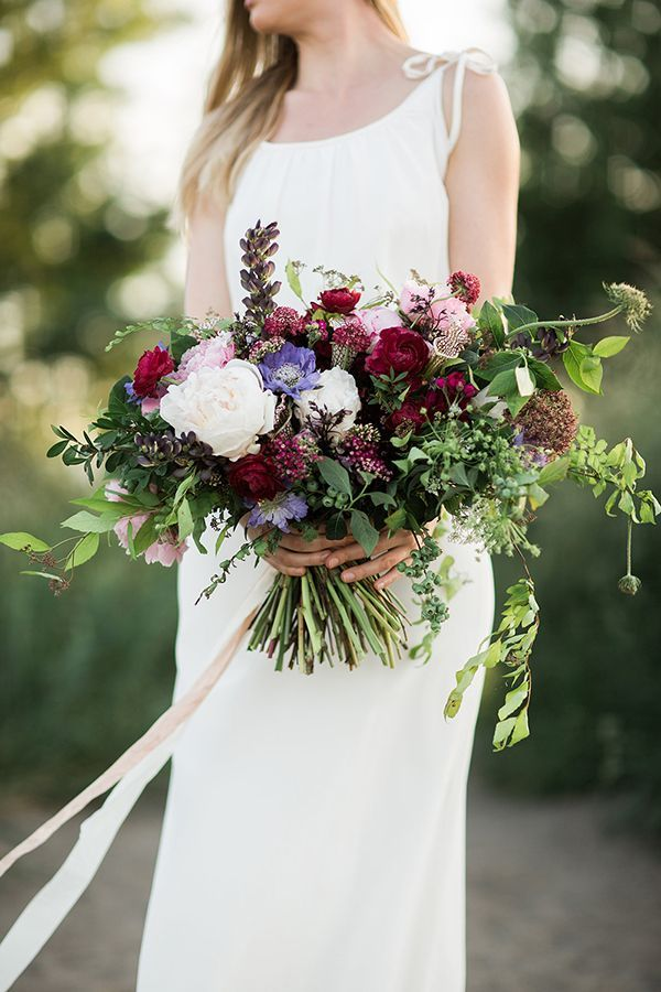 Loosely arranged by Christopher David for a just-gathered look, this jewel-toned bouquet included peonies, ranunculi, scabiosas, blueberries, Queen Anne's lace, and lupin | Photo by Jason Wasinger