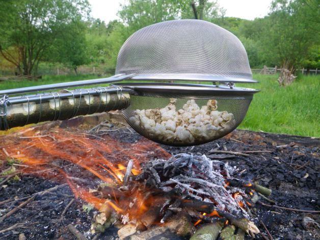 kampvuur popcorn: bindt met ijzerdraad één zeef met het handvat aan een lange tak; de tweede zeef komt er bovenop; ze zitten met de haakjes op de kop aan elkaar vast; maïs erin en boven het vuur! (tutorial)