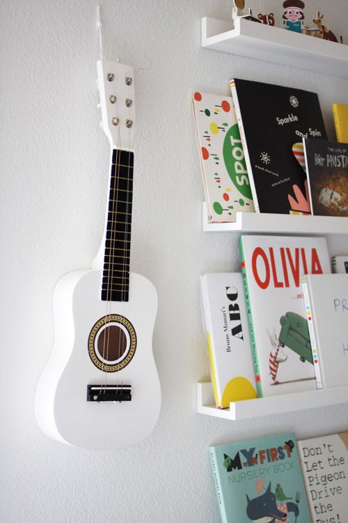 Narrow book shelves to display and rearrange books. Painted guitar is great - but one you could pull off the wall and play would be even better.