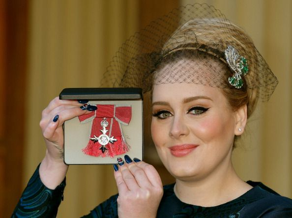 Adele Adkins MBE holds her MBE award for services to music after it was presented to her by the Prince of Wales at an Investiture ceremony at...