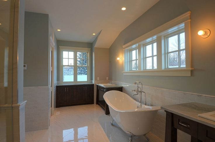 Gorgeous white glossy tiled bathroom with foot claw tub | Calgary