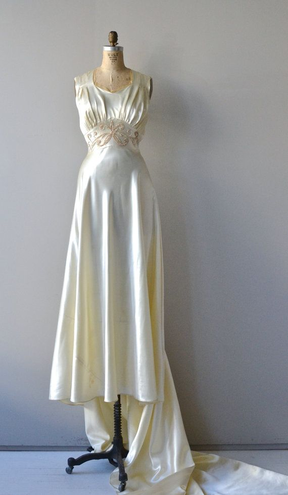 Vintage late 1930s ivory satin wedding gown with sleeveless empire waist bodice, graceful pearl detail at the waist, extending train and side metal zipper. --- M E A S U R E M E N T S ---  fits like: small/medium bust: 36 waist: fits 27-30 hip: free length: 60 at front with long extending back train brand/maker: n/a condition: very faint discoloration at the bottom of the hem and a smaller area on the train, quite faint, see last photo  ✩ layaway is available for this item  to ensure a good…