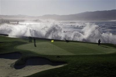 Greenskeepers look on as waves crash over the seawall on the 18th hole of the Pebble Beach Golf Links during a practice round at the AT&T; Pebble Beach National Pro-Am PGA Tour golf tournament in Pebble Beach, Calif., Wednesday, Feb. 8, 2012. ((AP Photo/Eric Risberg))
