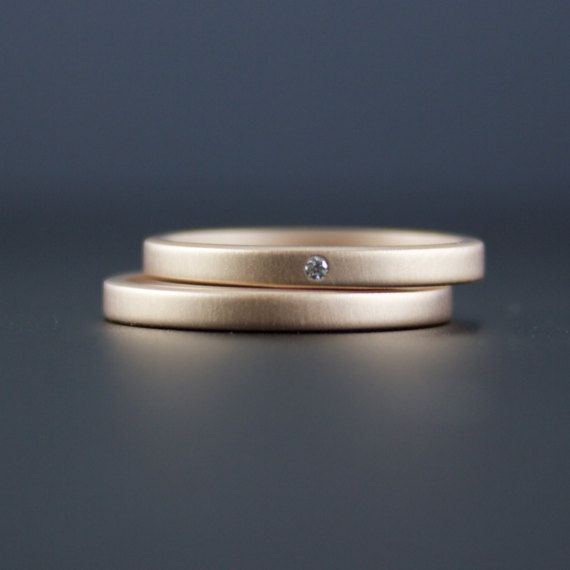 Un set di due anelli di finitura opaca oro rosa 18 carati artigianali. Un anello ha un piccolo diamante bianco filo insieme nella band. Un anello è una semplice fascia corrispondente. Le misure di anelli circa 2 mm di larghezza e 1,25 mm di profondità. Il diamante bianco è un punto (1,3 mm), VS qualità, colore G-H, Rotonde sfaccettate in genuina. Quando possibile lavoro con armonia riciclato diamanti, sempre eco-amichevole, non-conflitto gemme. Loro è il metallo recuperato tutto. Questi ...
